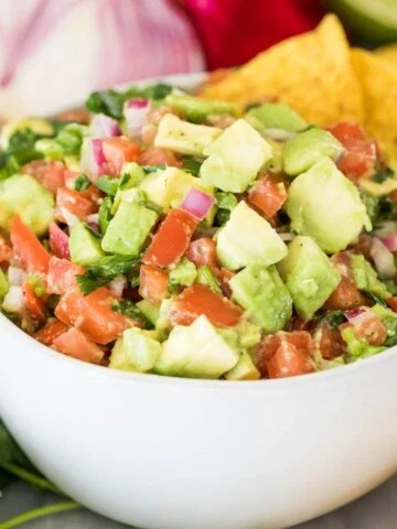 avocado salsa in white bowl with corn chips