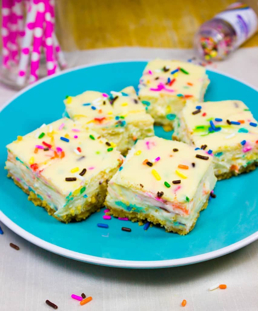 sprinkle covered cheesecake squares on blue plate