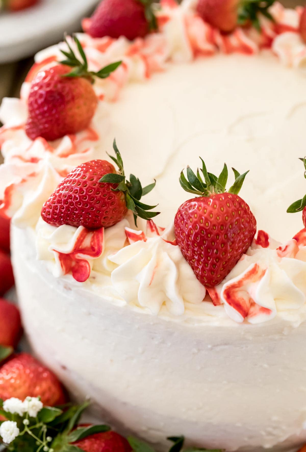 white iced cake with red strawberries
