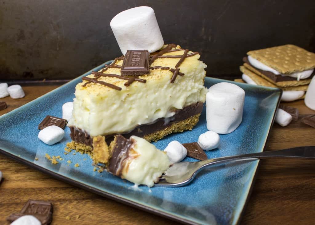 slice of S'mores Cheesecake on blue plate with fork