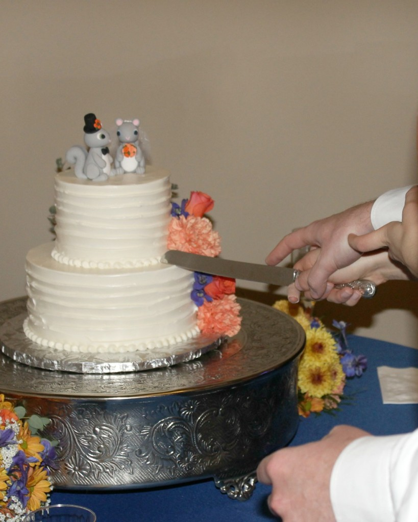 Slicing into a two tier wedding cake with squirrel bride and groom cake toppers