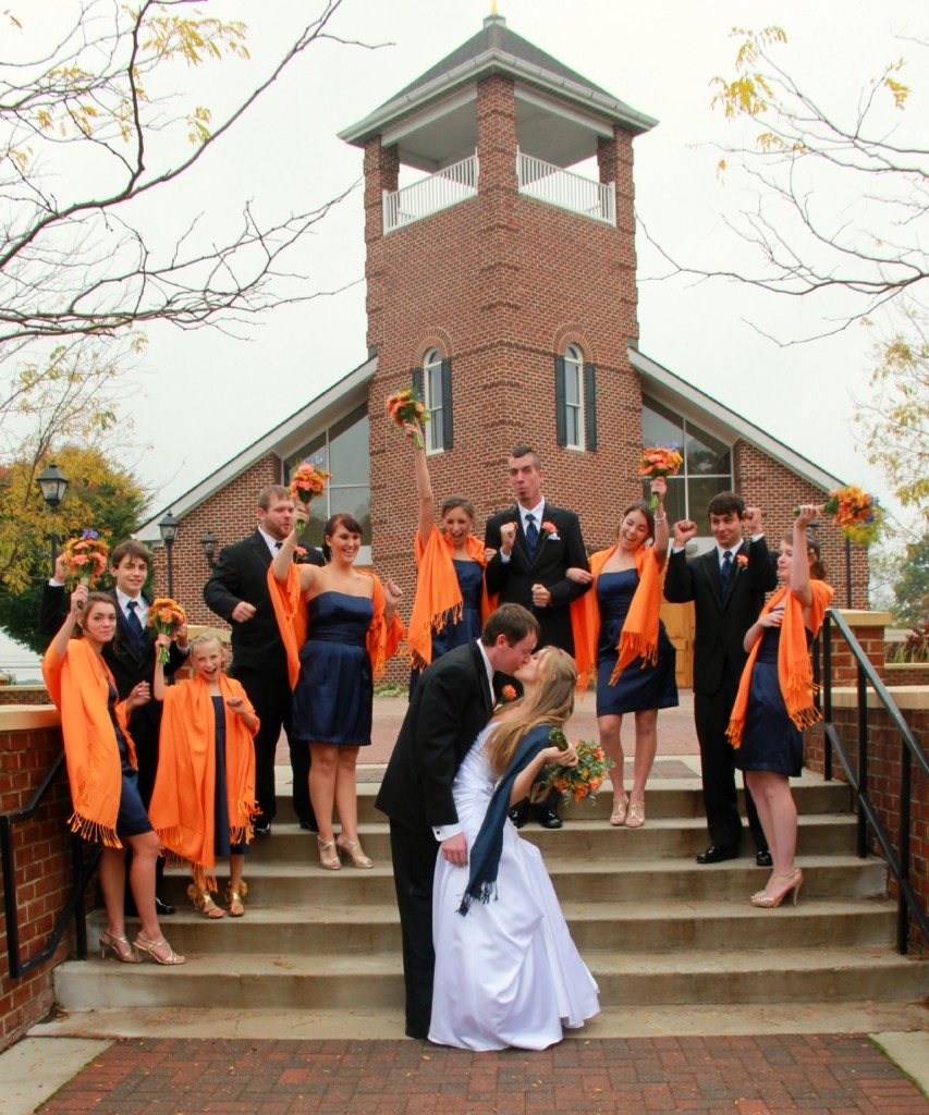 bride and groom kiss in front of church, bridal party celebrates in background