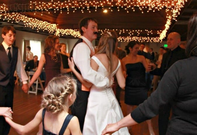 bride and groom (wearing a fake moustache) dance at wedding reception
