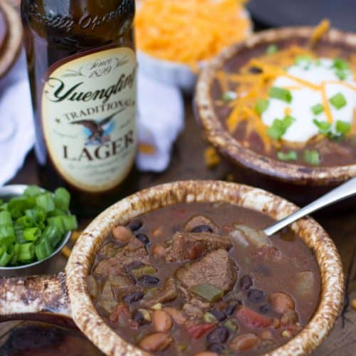 Steak and beer chili in a bowl, bottle of beer in background