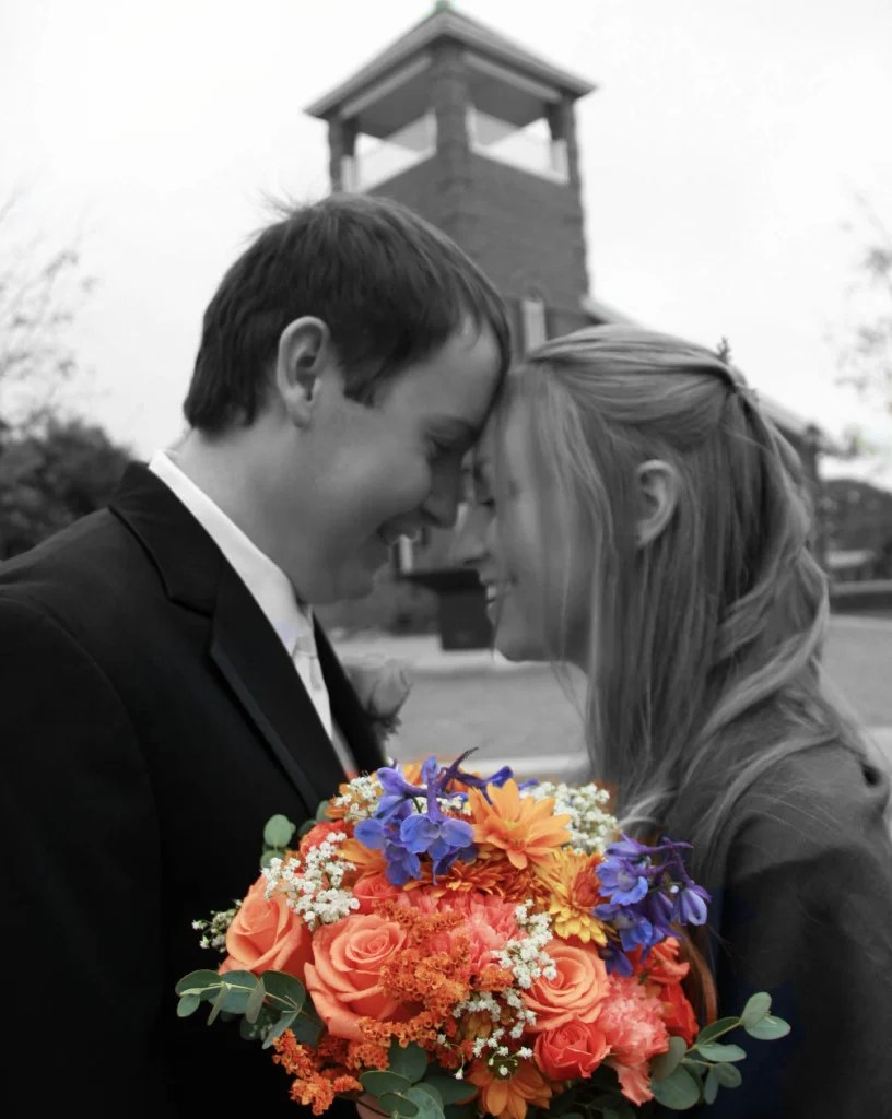 bride and groom in black and white with flower bouquet in color in foreground
