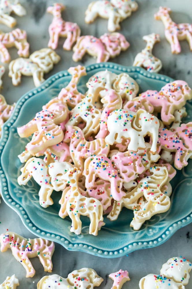 Pink and white frosted animal cookies on a blue plate