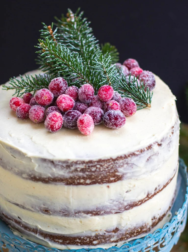 3 layer cake topped with sugared cranberries and pine clippings