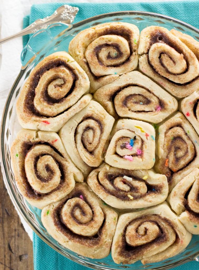 Overhead: sprinkled cinnamon rolls in pie plate