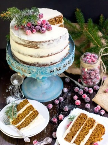 Frosted Gingerbread layer cake on a blue cake stand with slices on white plates