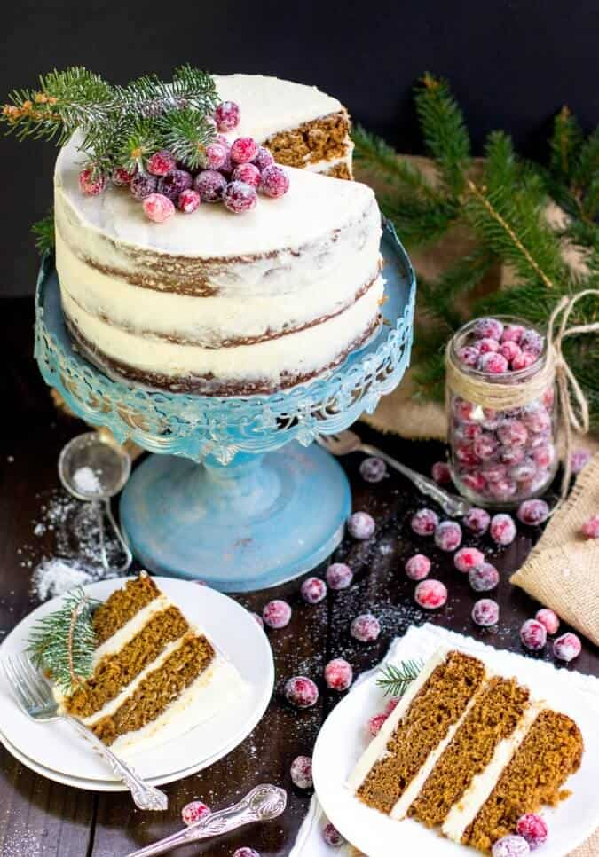 gingerbread layer cake on blue cake stand with slices on white plates
