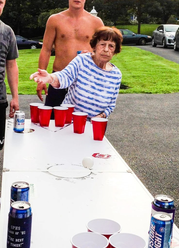 great-grandmother playing beer pong with shirtless college student in background