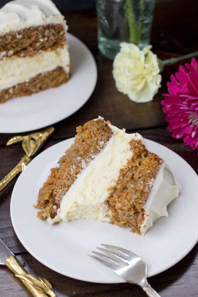 Slice of carrot cake cheesecake on a white plate