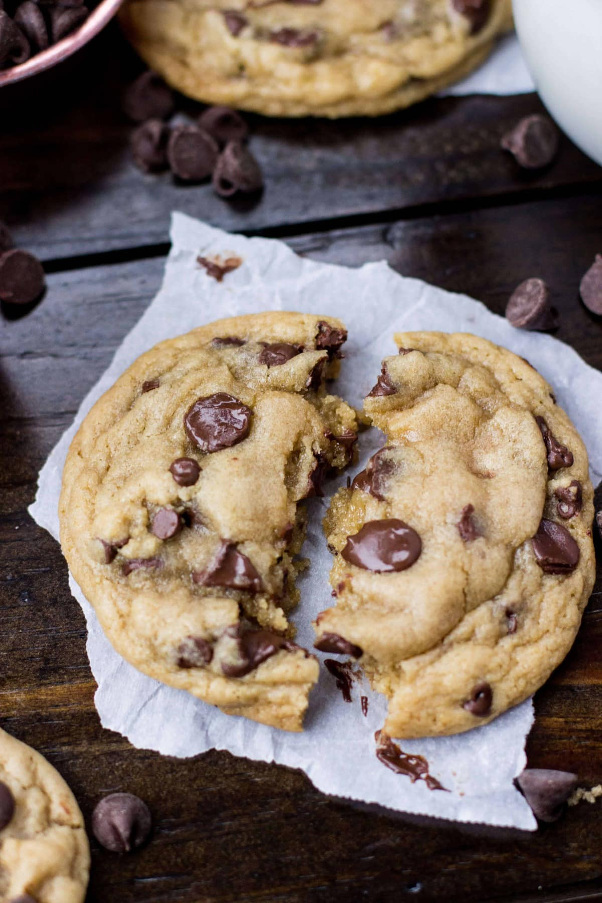 Worst chocolate chip cookie on parchment paper on a wood surface, broken in half