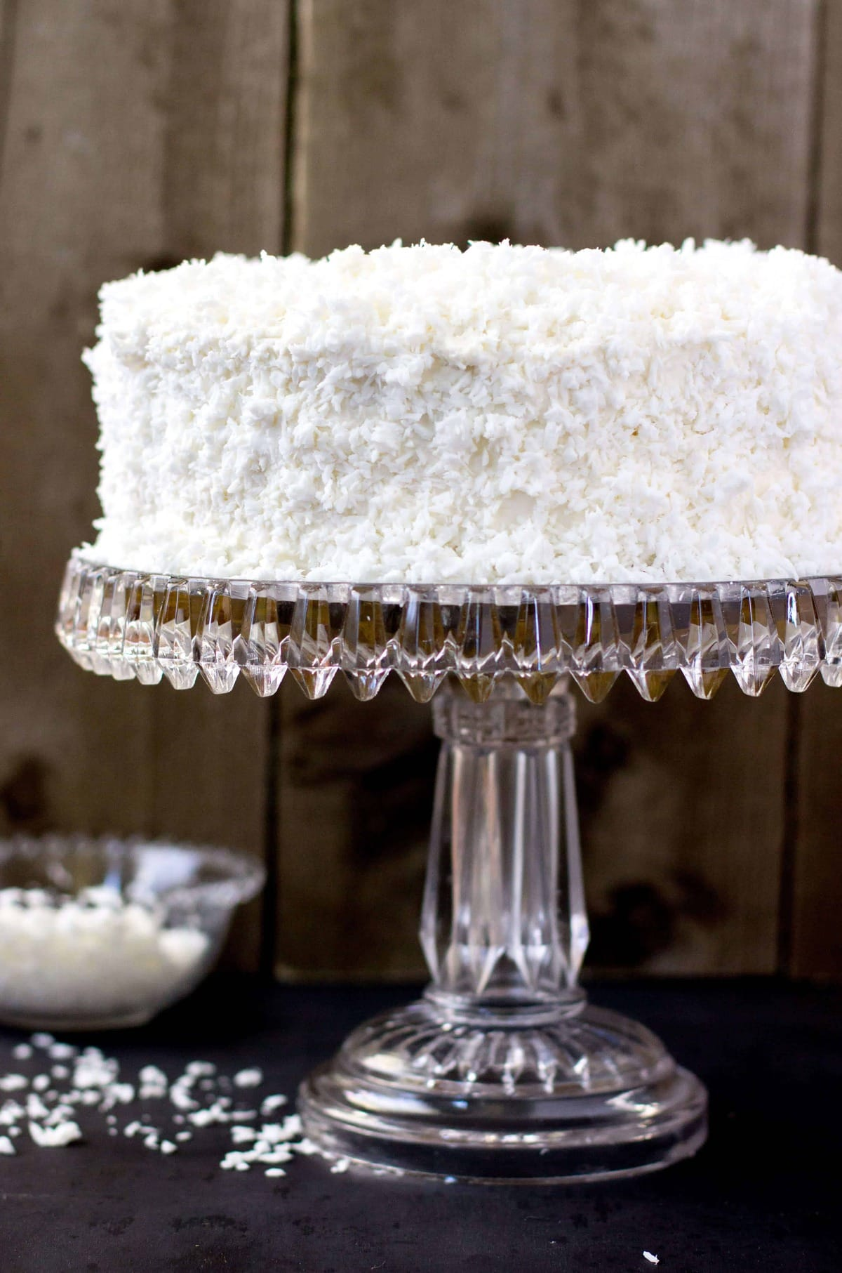Frosted coconut cake on crystal cake stand