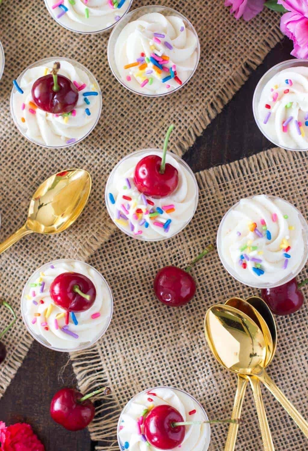 Overhead of cake batter dessert shooters topped with cherries