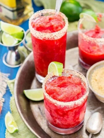 Strawberry margarita granita with a slice of lime, on a silver serving tray