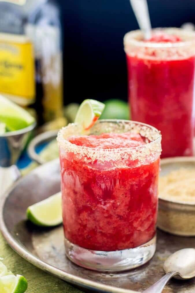 Strawberry margarita granita in a glass with a slice of lime