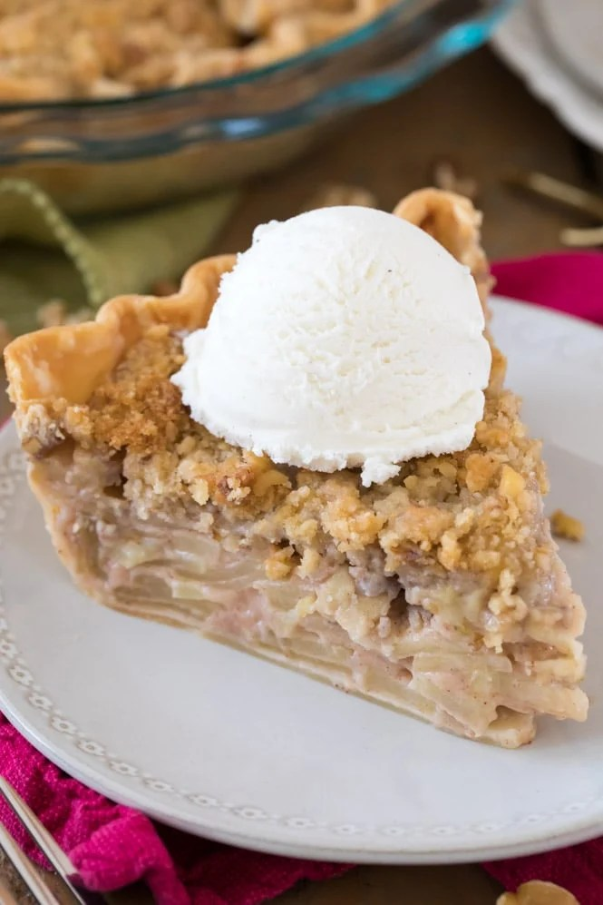 Slice of apple pie topped with vanilla ice cream on white plate