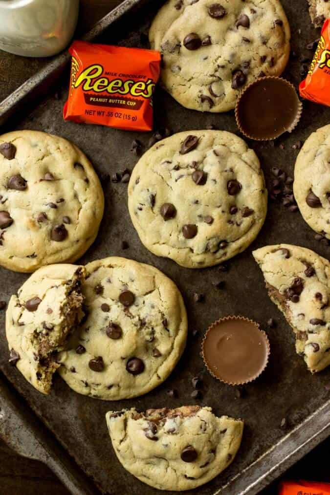 Peanut butter cup stuffed chocolate chip cookies on a baking sheet with reeses peanut butter cups and mini chocolate chips