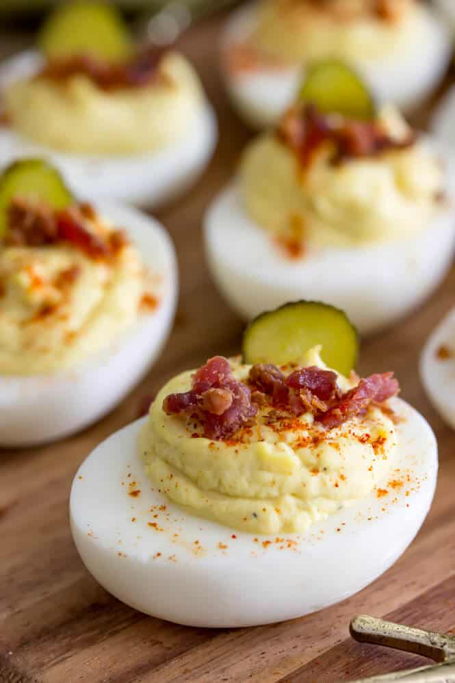 Deviled eggs topped off with paprika, bacon, and sweet pickle slices