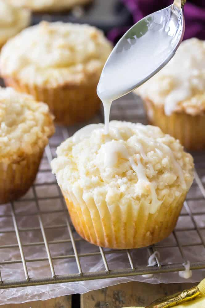 Glaze being drizzled over lemon muffin