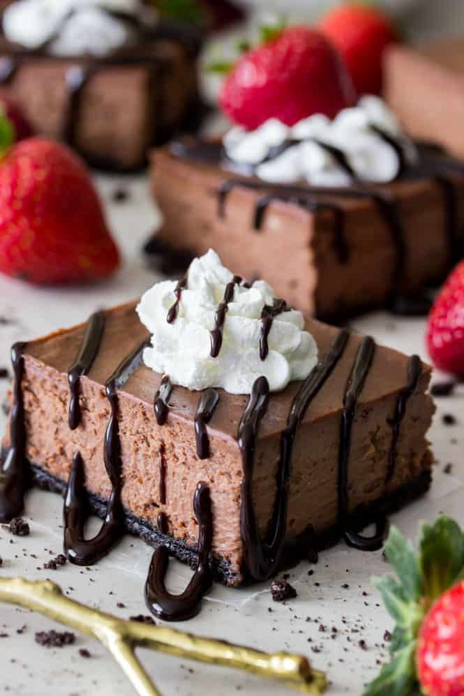 Chocolate cheesecake bar, drizzled with chocolate, topped with whipped cream and a strawberry