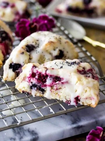 Triple berry scones drizzled with glaze on cooling rack