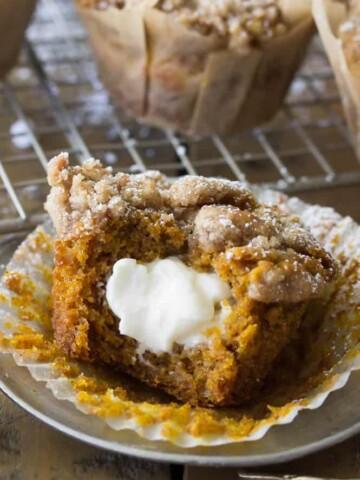 Cream cheese pumpkin muffin with bite missing, revealing cream cheese center