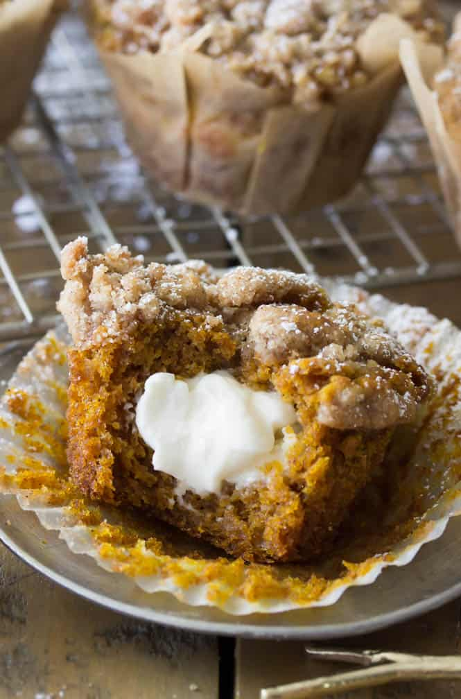 Cream cheese pumpkin muffin with bite missing, revealing cream cheese center