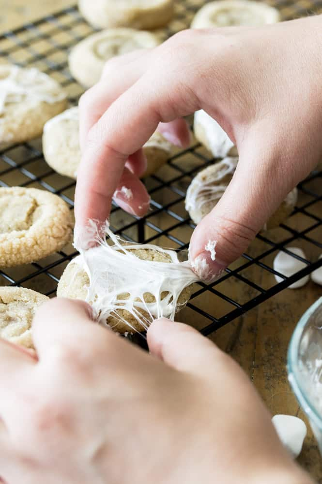 Hands stretching marshmallow over cookie to make spiderweb