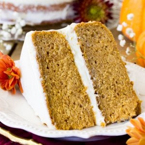 Slice of frosted pumpkin layer cake on plate