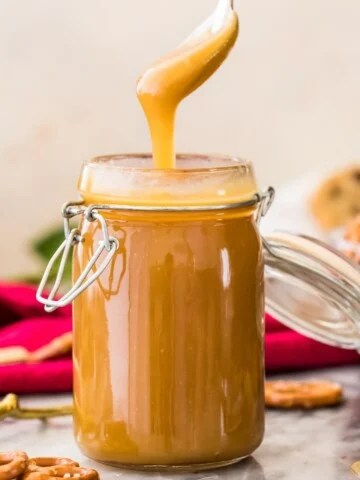 golden caramel sauce dripping off spoon into glass container