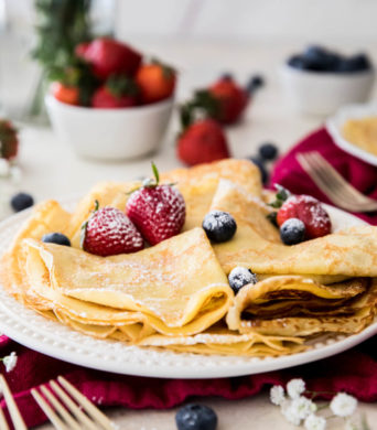 folded crepes with powdered sugar and strawberries on a white plate
