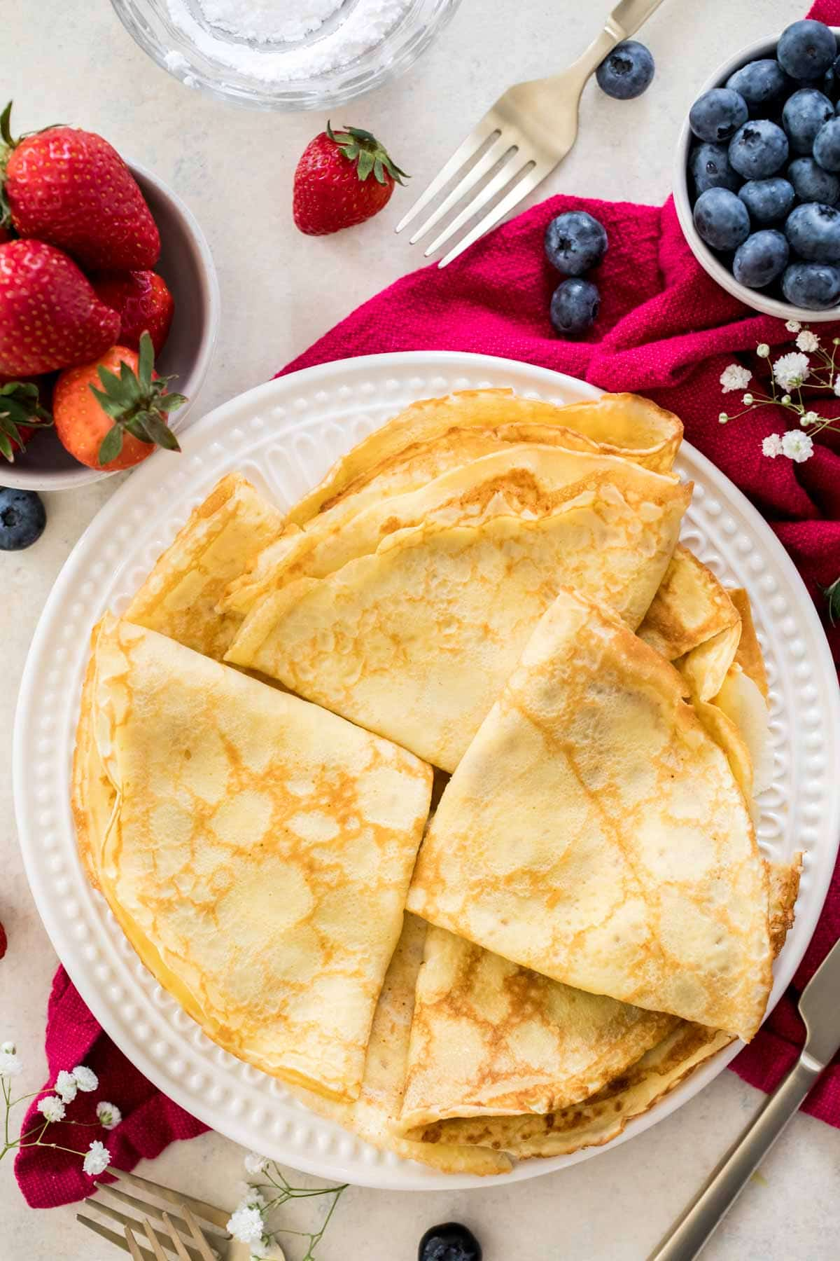 folded crepes on a white plate on a red napkin
