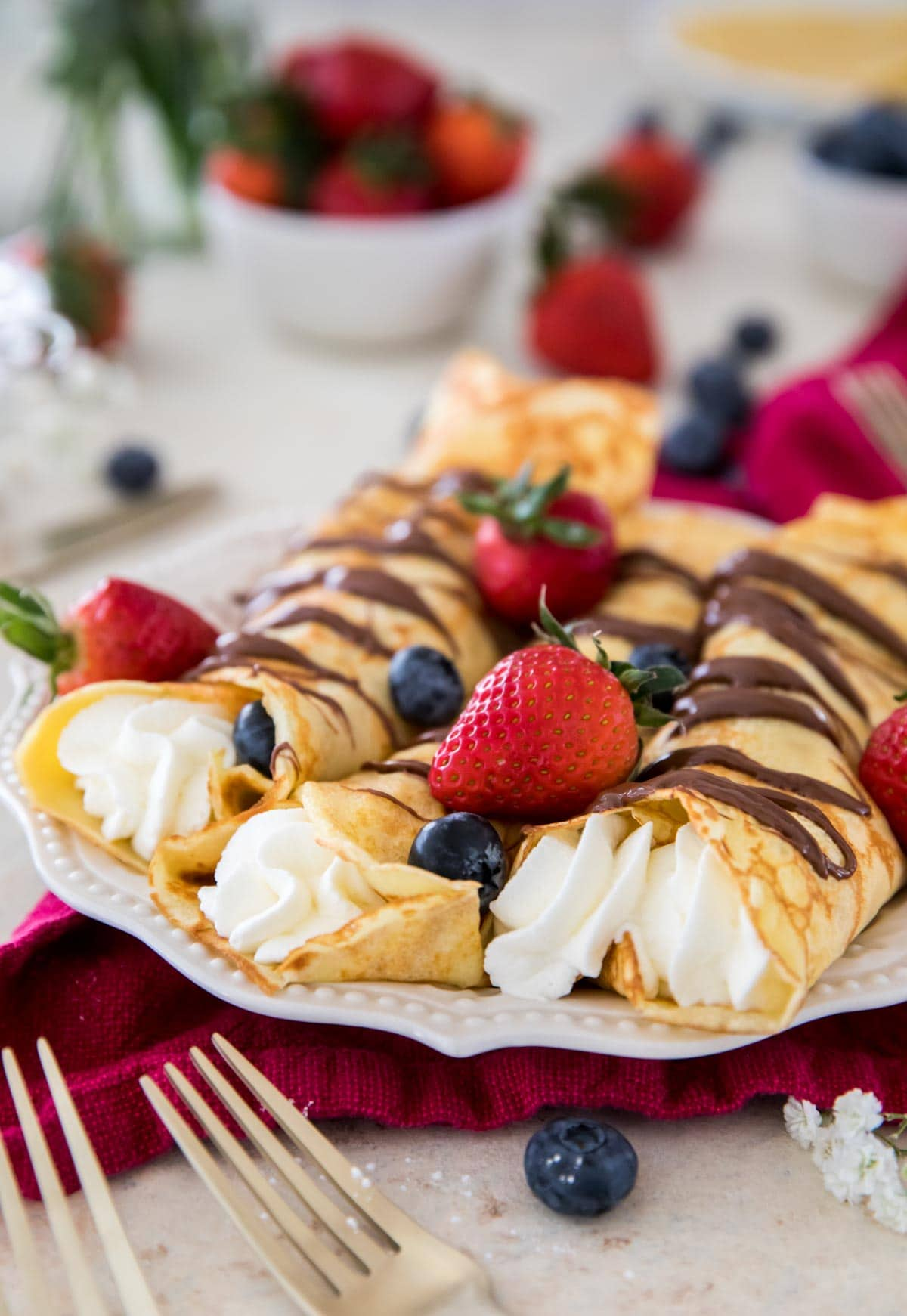 Crepes filled with whipped cream, drizzled with nutella and topped with berries
