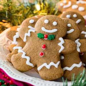 Stack of decorated gingerbread cookie men on plate
