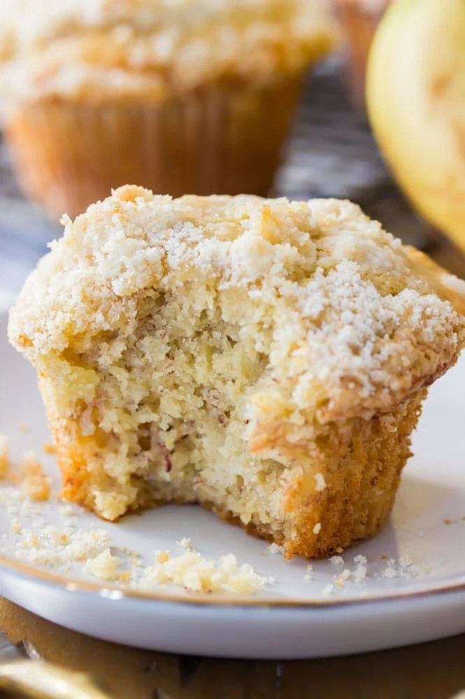 Banana muffin with bite out of it (to show soft fluffy center) on white plate