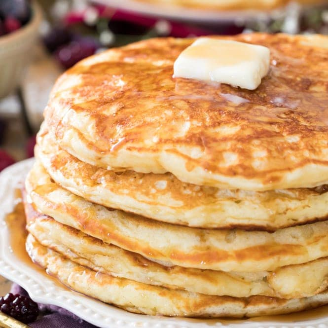 Stack of buttermilk pancakes topped with butter and syrup