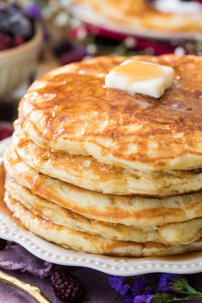 Stack of fluffy homemade buttermilk pancakes on white plate