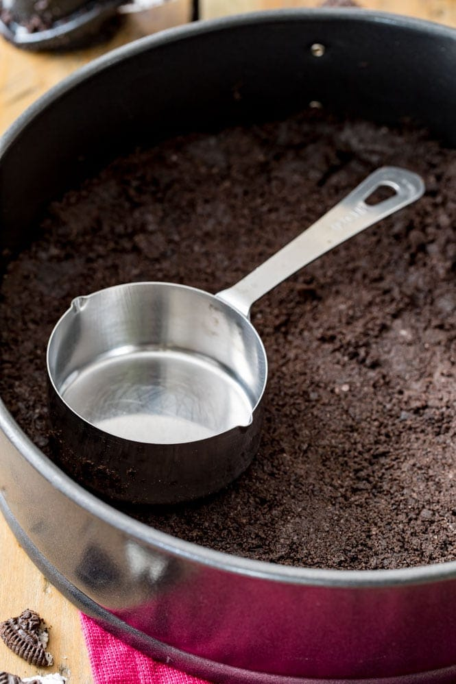 Oreo crust being tamped down with a measuring cup