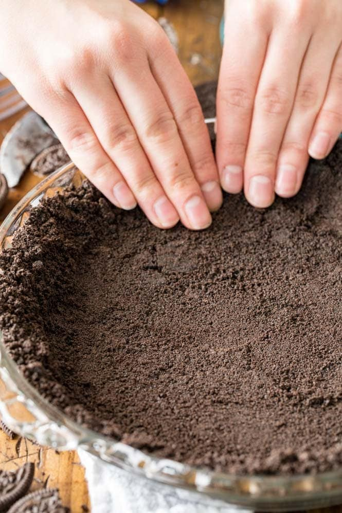 Hands pressing oreo cookie crumbs into pie plate