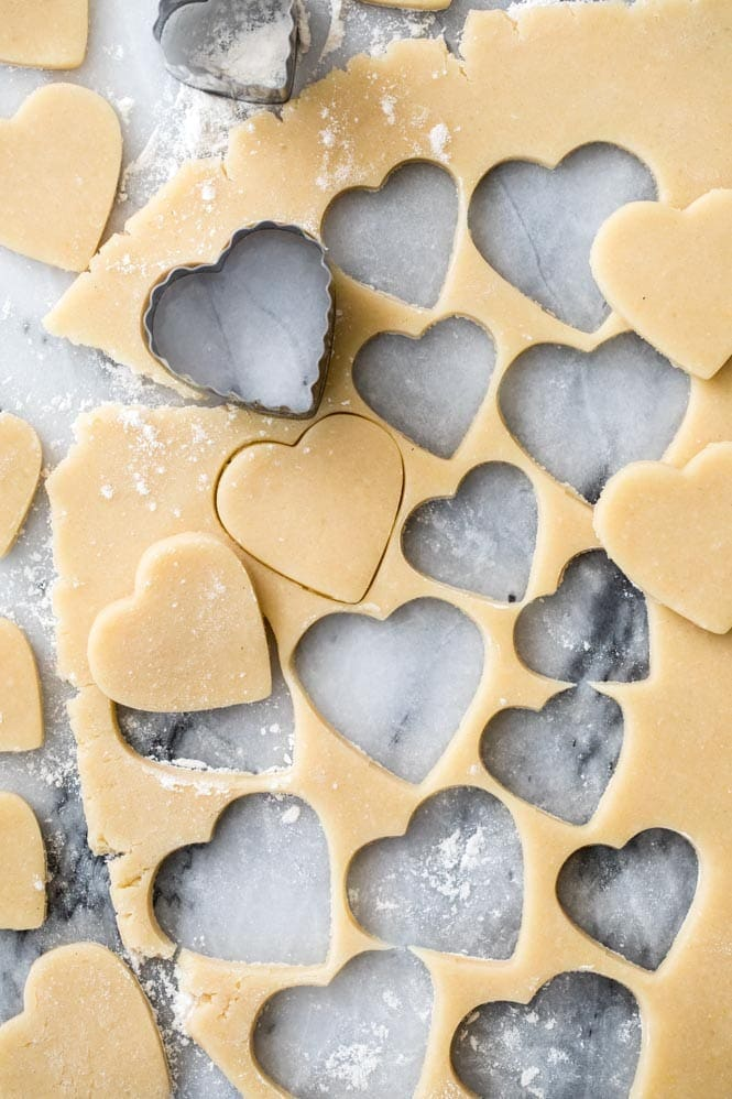 Sugar Cookie Dough being cut into heart shapes