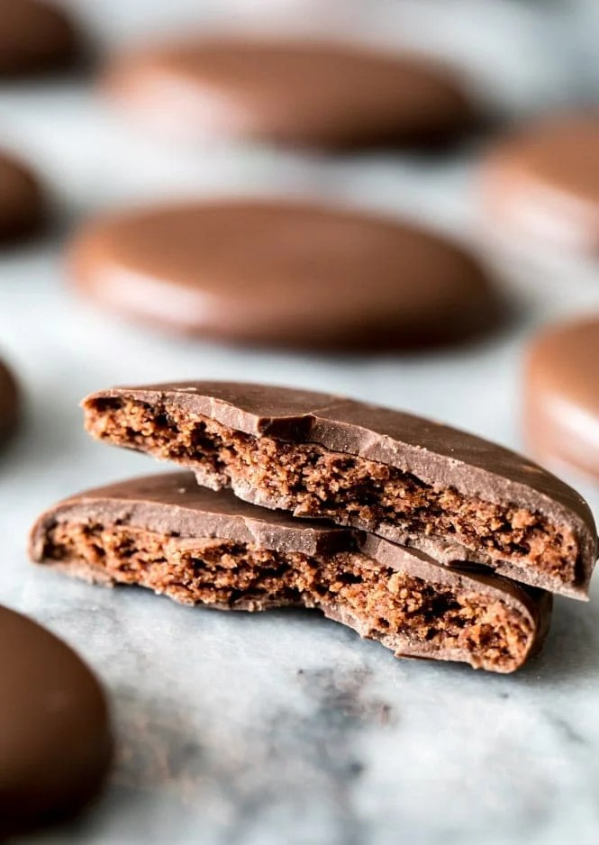A thin chocolate wafer cookie coated in chocolate, broken in half to showcase the crisp center and chocolate cloak