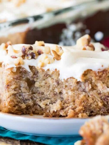 Slice of banana cake with frosting and chopped nuts