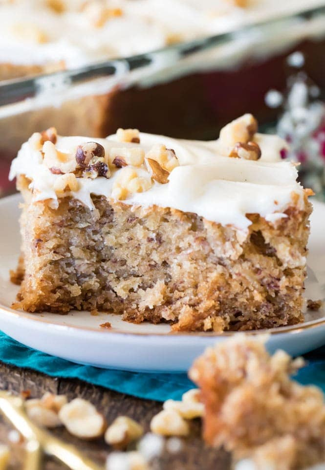 slice of banana cake with cream cheese frosting and nuts