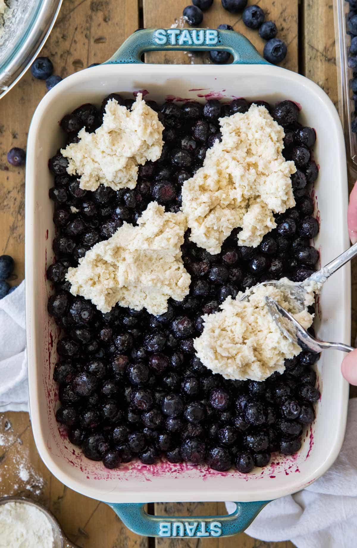 spooning cobbler batter over blueberries