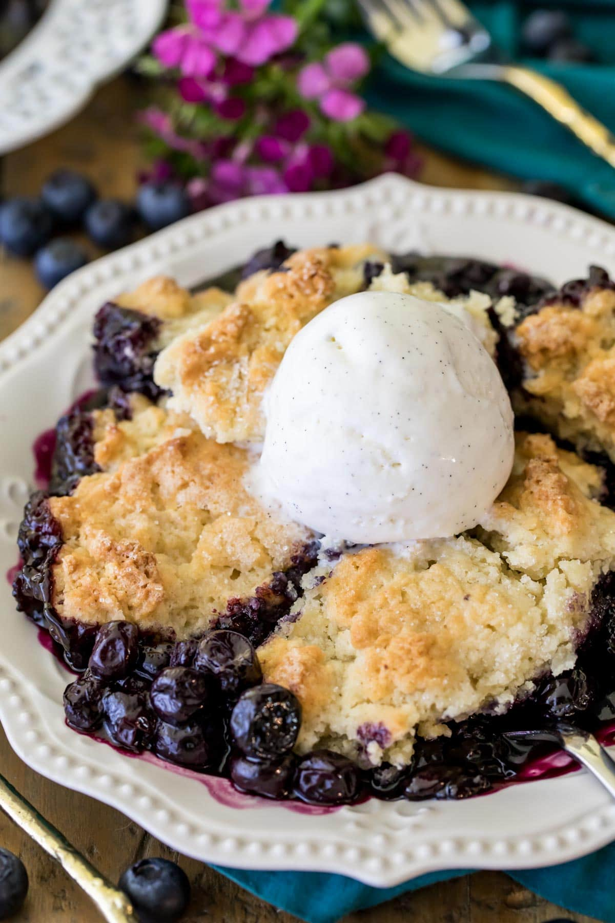 blueberry cobbler on white plate with ice cream