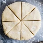 Scone dough shaped into disc, cut into 8 pieces