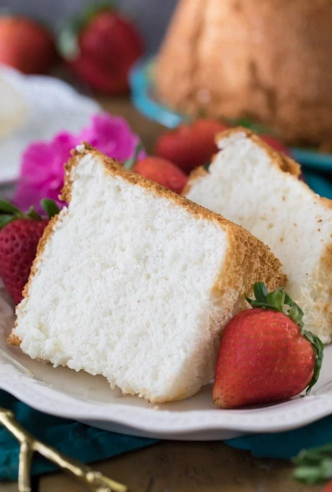 Two slices of angel food cake on white plate with strawberries