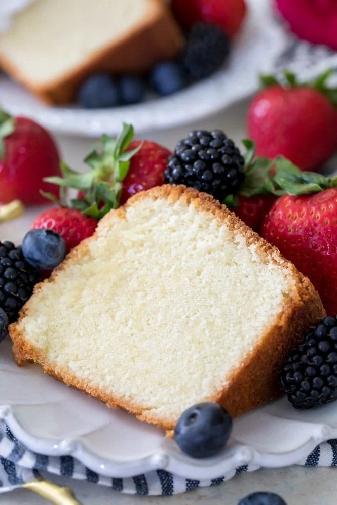 slice of pound cake surrounded by berries on white plate